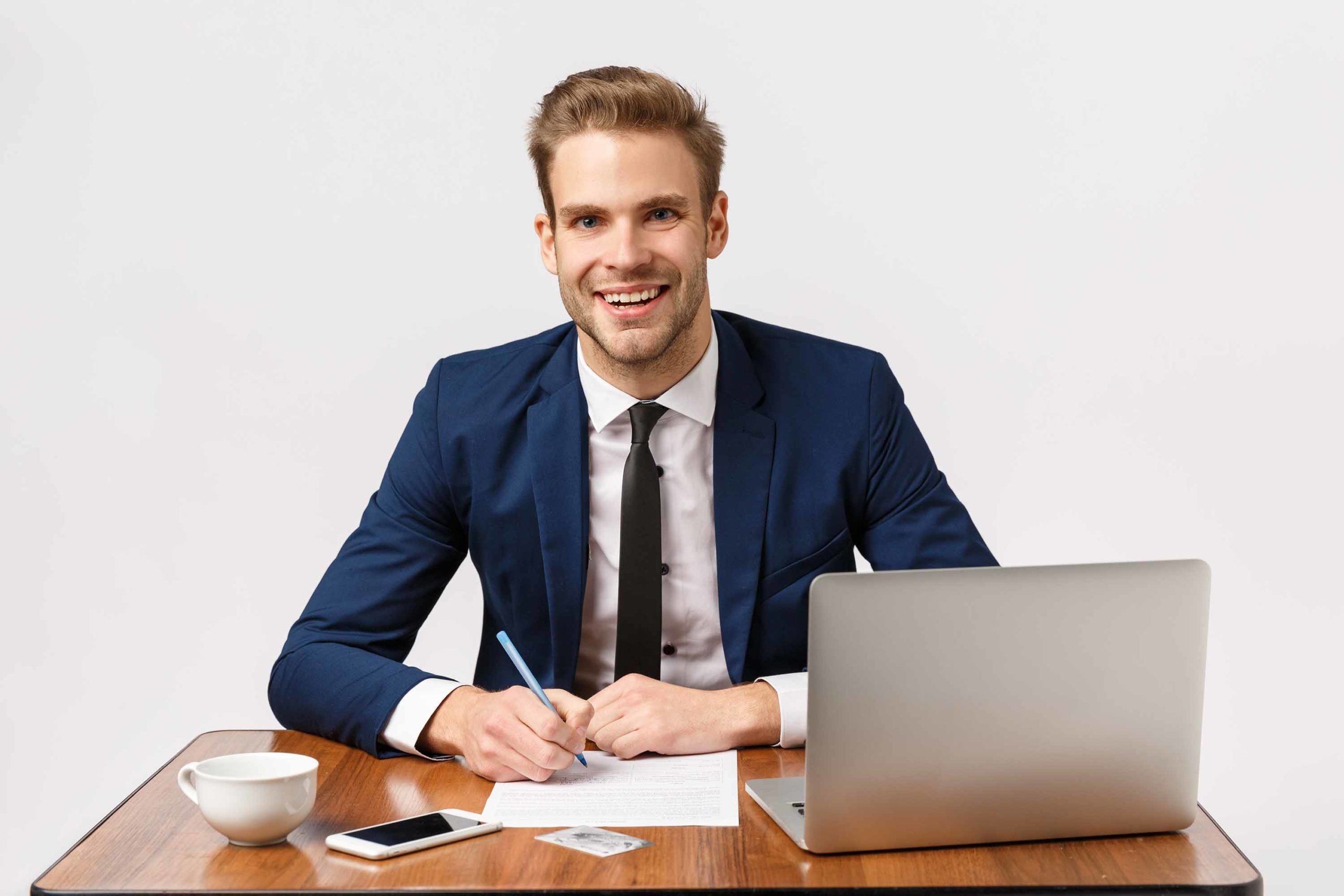 Business, office and corporate concept. Handsome, cheerful blond bearded guy in classic suit, sitting table, company desk with laptop, papers smartphone and cup coffee, write report, manage business.